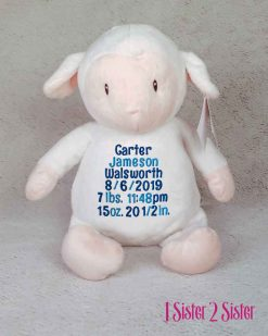 Lamb plush toy with birth stats.